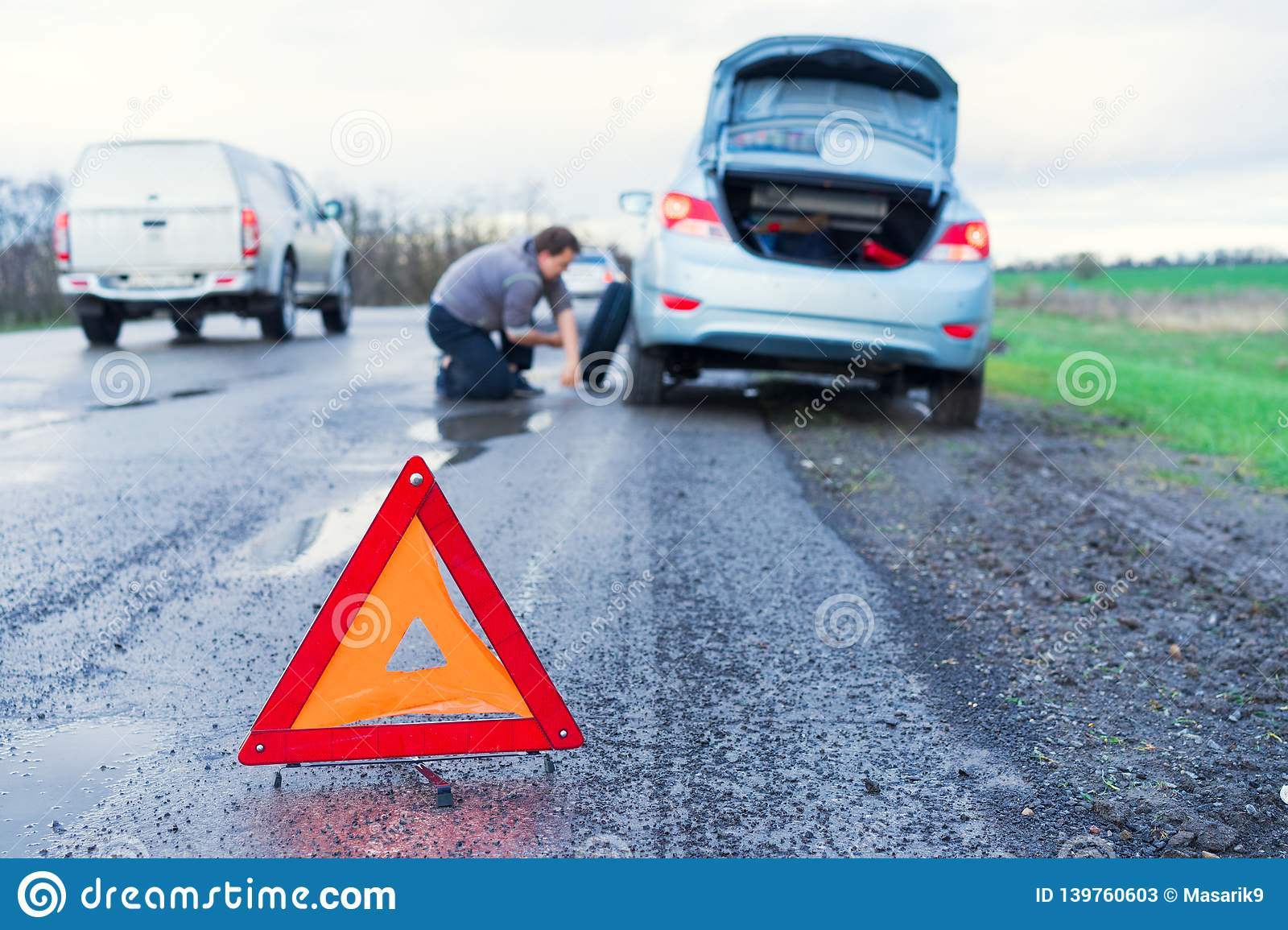 Road accident sign on the background man replaces flat tyre on road. Car tire leak because of nail pounding