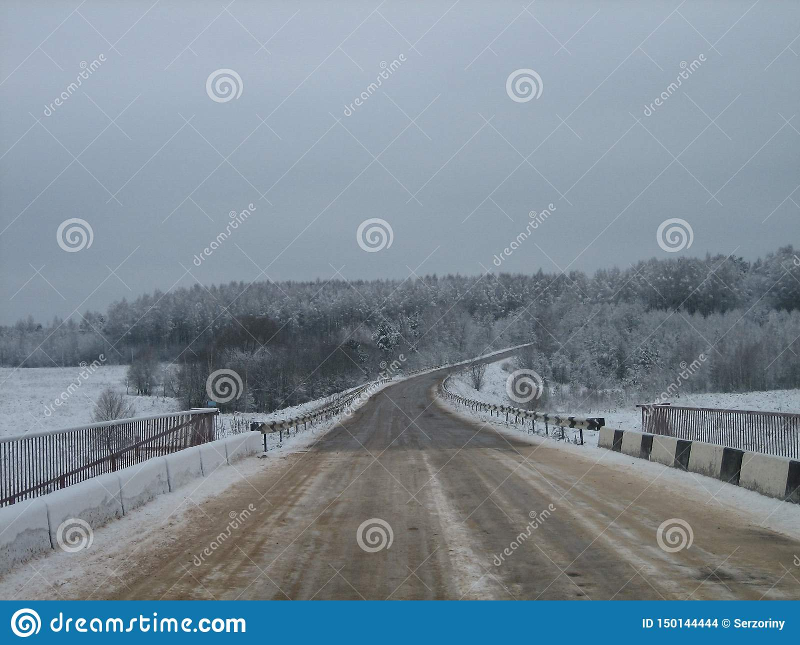 Road bridge over the river in the forest edge in winter on a gray cloudy day