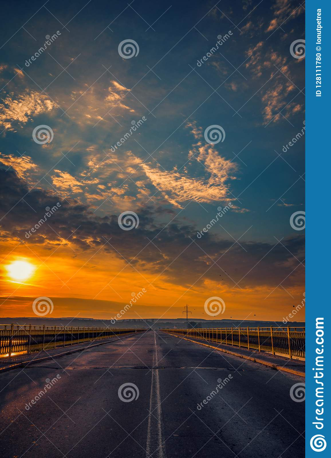 Road bridge over a river at sunrise against a blue sky with clouds