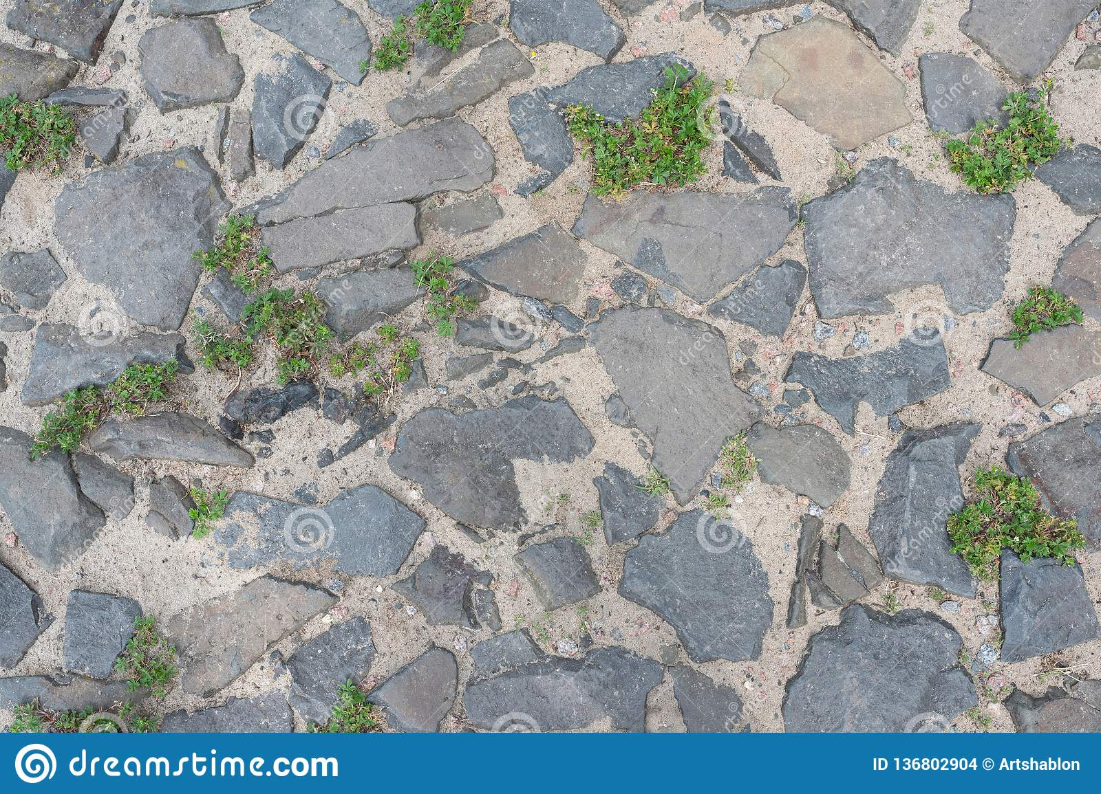 Road with cobblestone and overgrown by grass. Top view