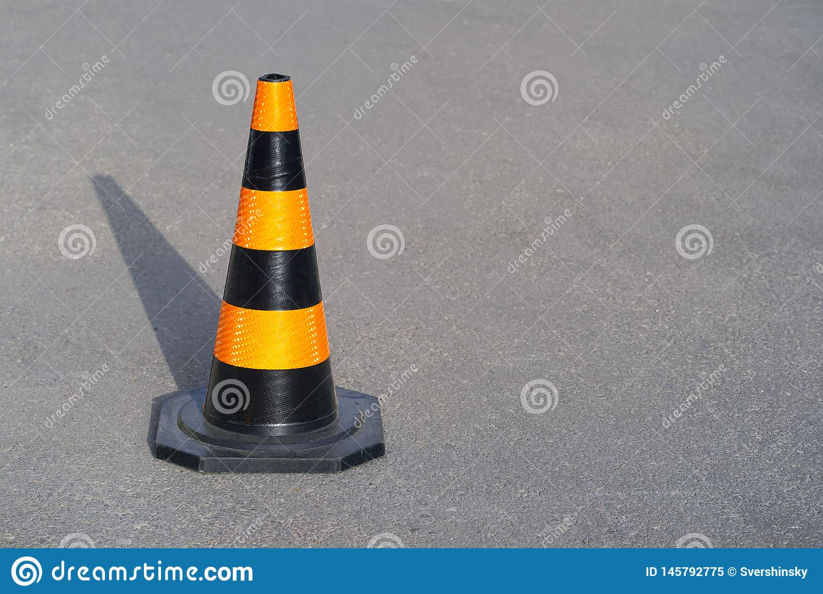 Road cone on the asphalt. Red caps on the road
