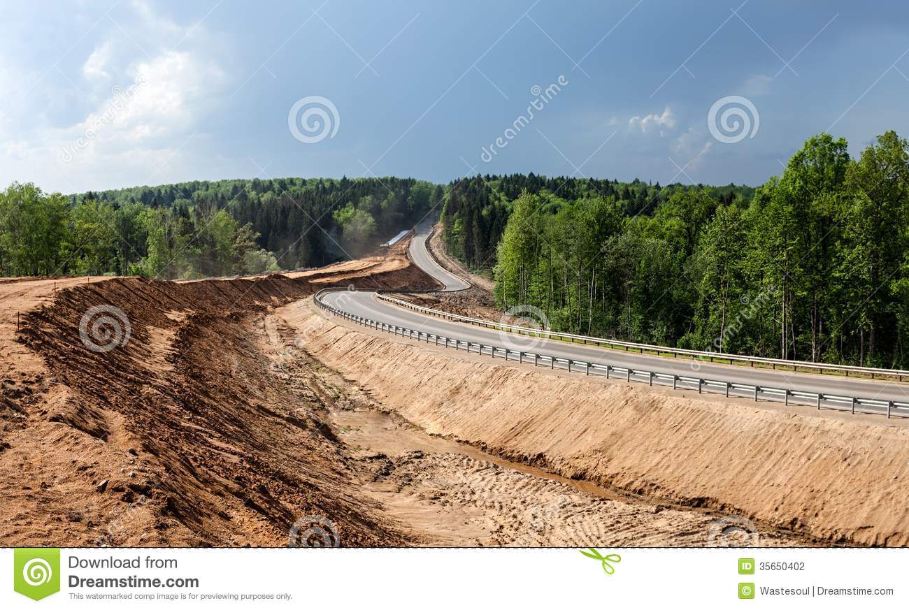 Construction of the embankment for exit from highway among the forest ...