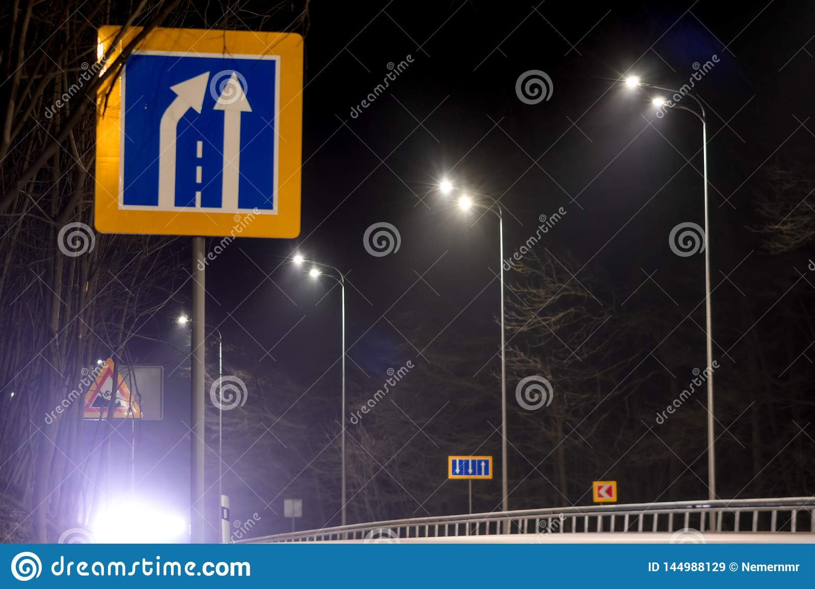 Road narrowing sign, street lighting, supports for ceilings with led lamps. concept of modernization and maintenance of lamps,