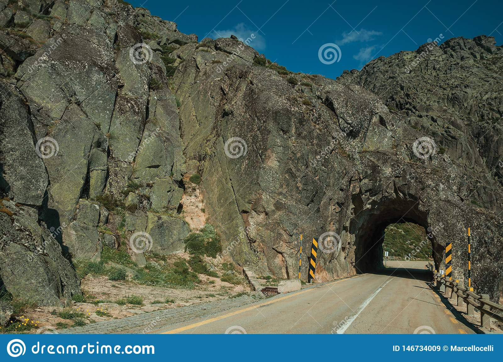 Road on rocky landscape passing through tunnel