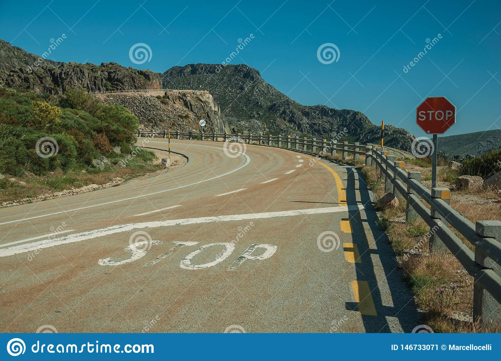 Road on rocky landscape with STOP traffic sign