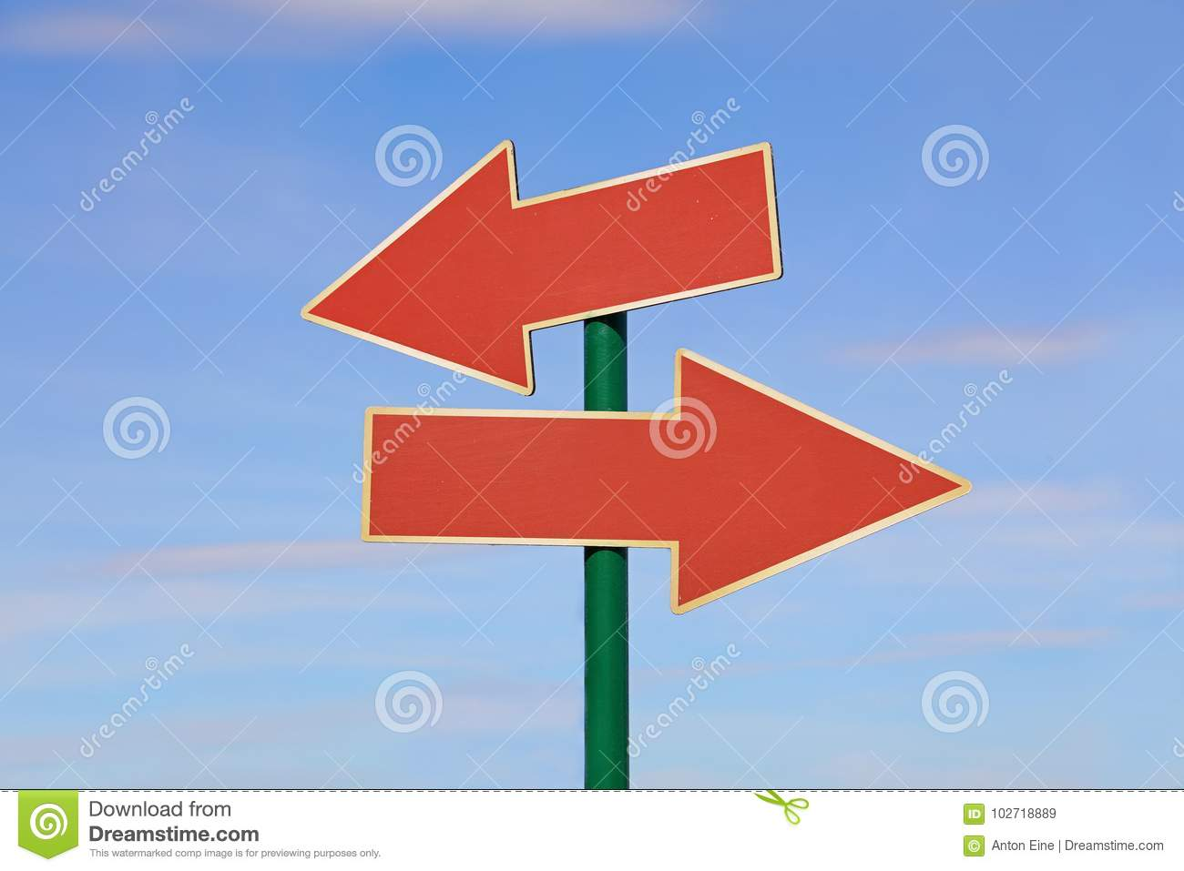 Road sign with two red arrows over blue sky