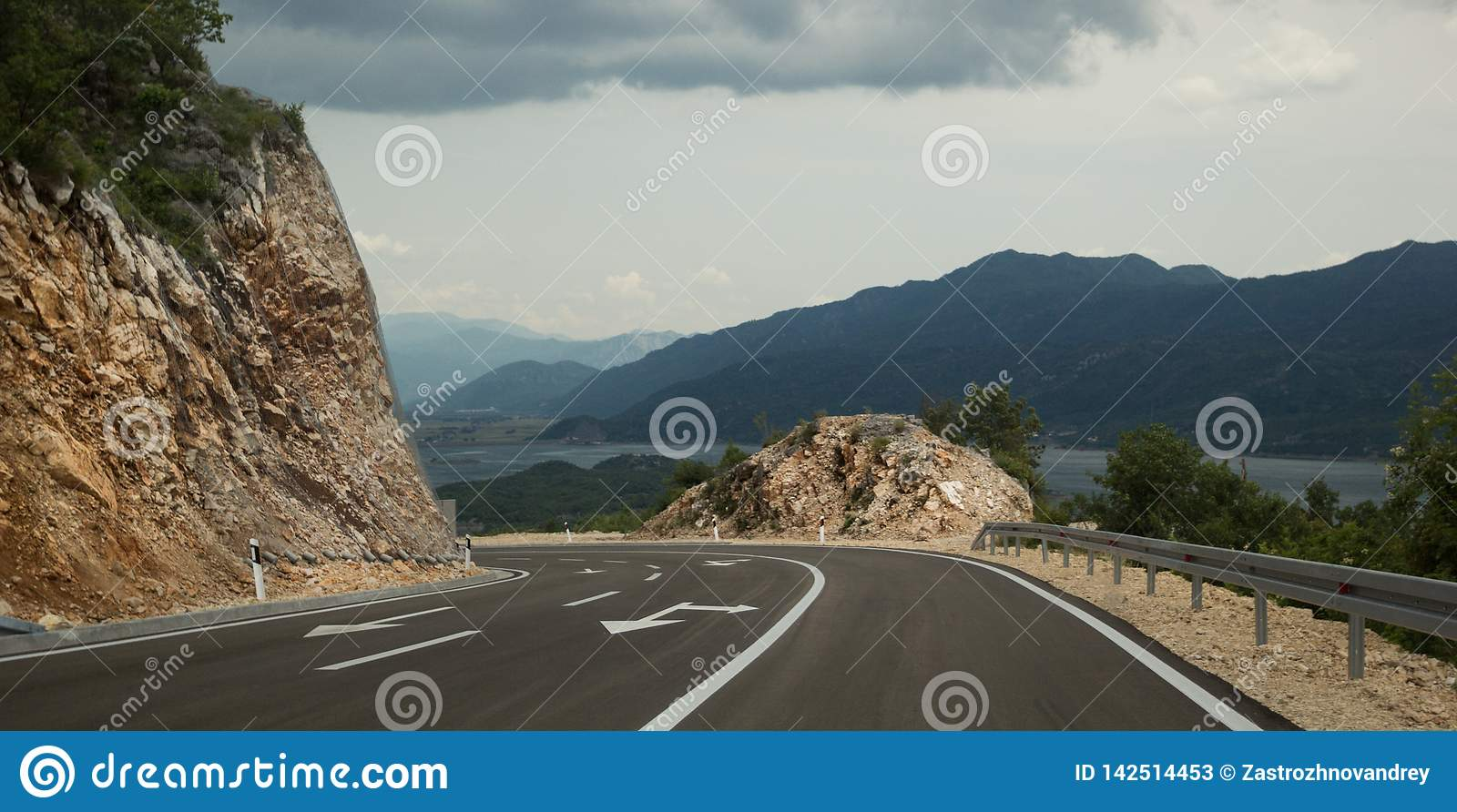 The road turns a mountain. Pointers on the pavement. Mountains, lake and clouds in the background