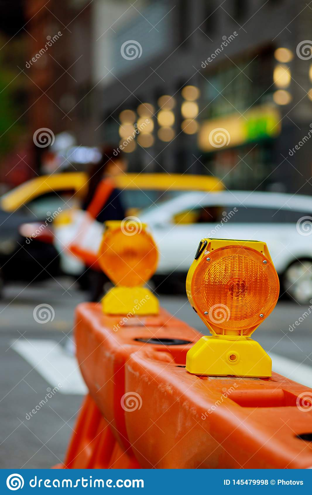 Roadblock or construction site lock with signal on a road. Red and white street barricade