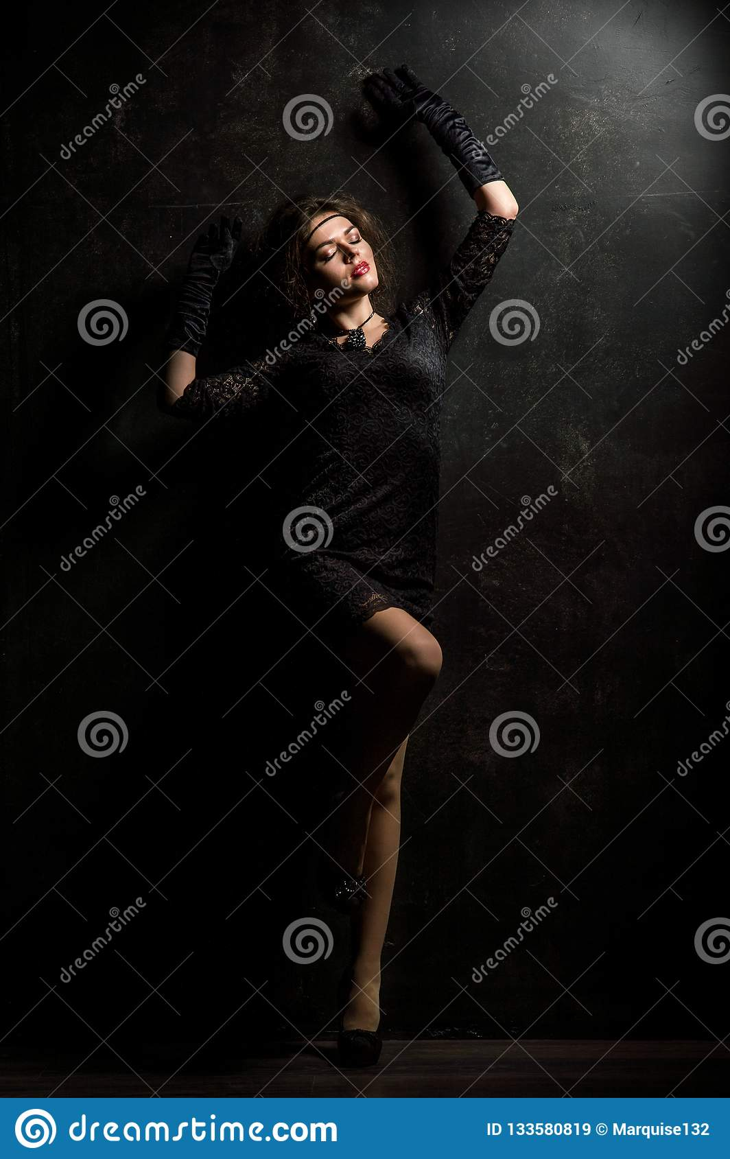 Roaring Twenties. Woman portrait in the style of Gatsby. Low key. Beautiful young woman in a lace black dress, posing sensually.
