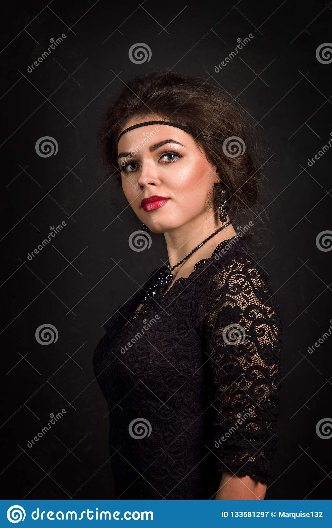 Roaring Twenties. Woman portrait in the style of Gatsby. Low key. Beautiful young woman in a black lace dress romantic looks.