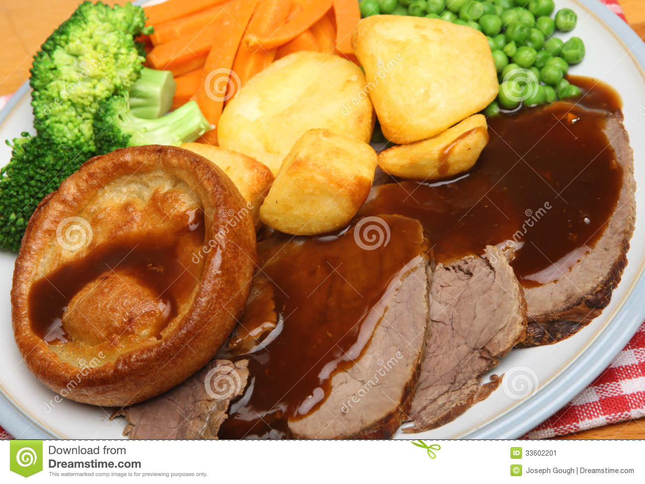 Roast beef Sunday dinner with Yorkshire pudding, vegetables and gravy.