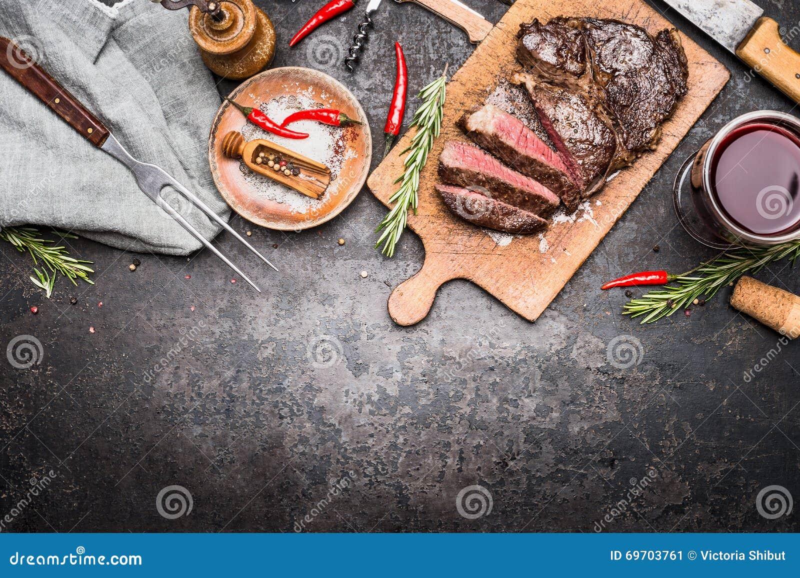Roasted切了在木切板的格栅牛排有在黑暗的葡萄酒金属背景,顶视图的酒、调味料和肉叉子的