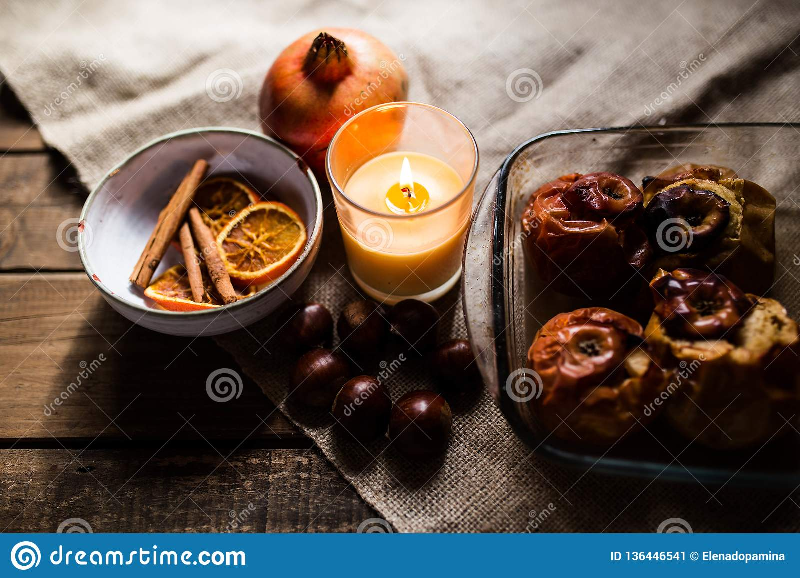 Roasted apples in a glass tray with chestnuts, cinnamon, orange and pomegranate
