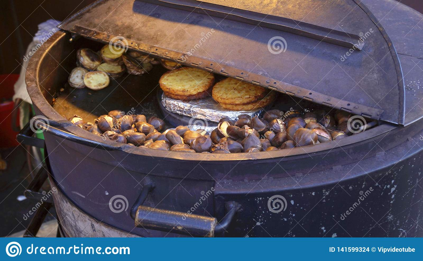 Roasted chestnuts are cooked in an iron barrel