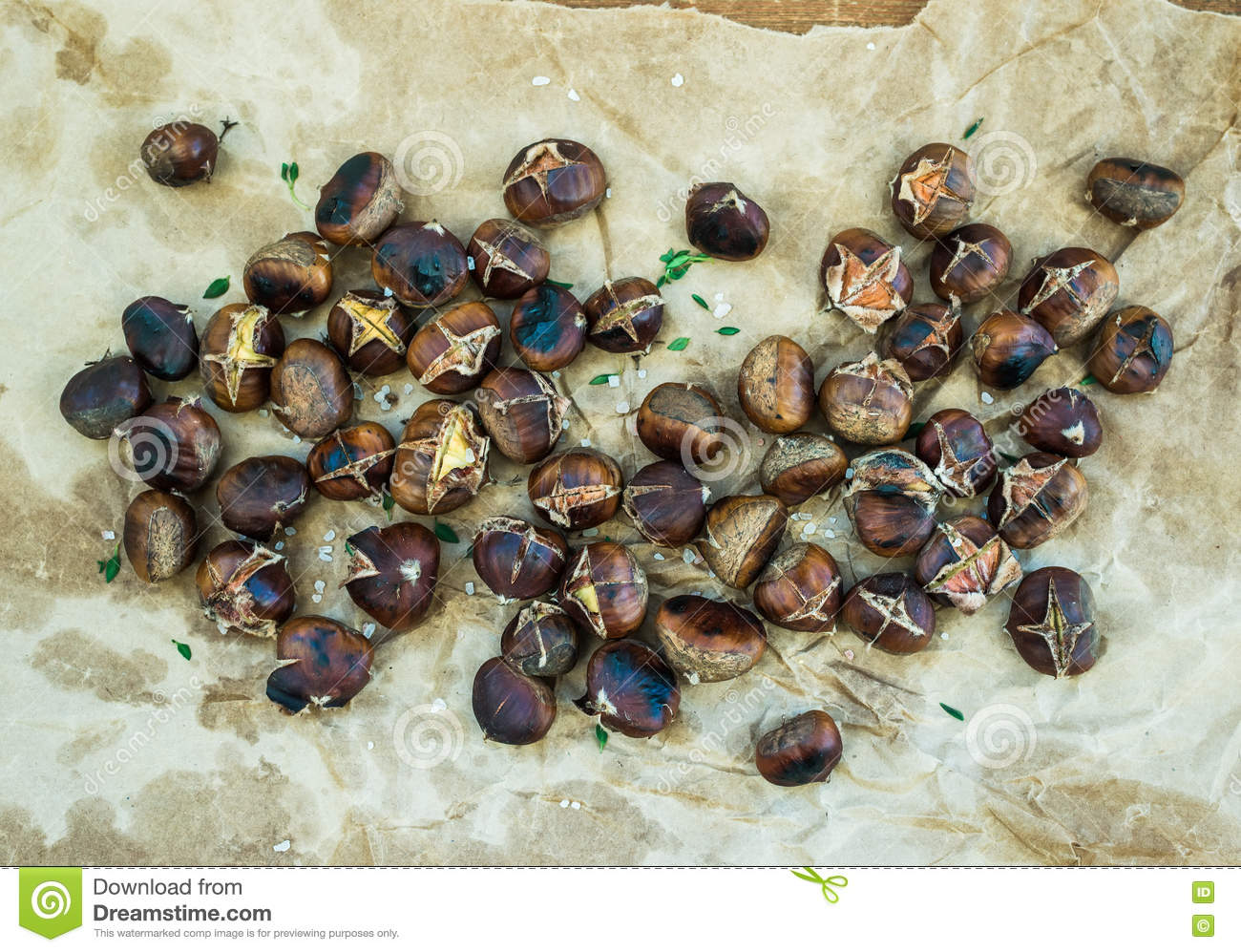 Roasted chestnuts on oily worn craft paper over rustic wooden background, top view.