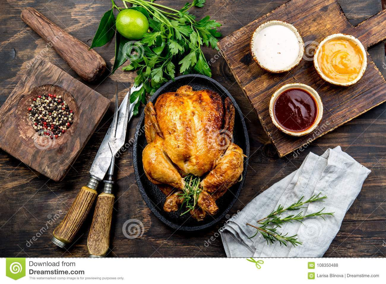 Roasted chicken with rosemary served on black plate with sauces on wooden table, top view.
