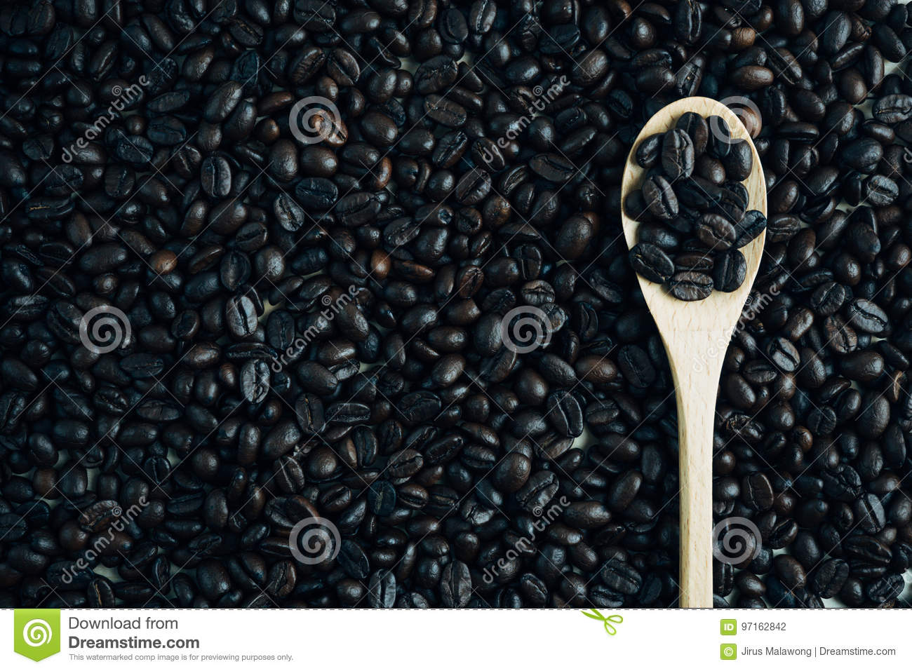 Roasted coffee bean background and texture with wooden spoon, co