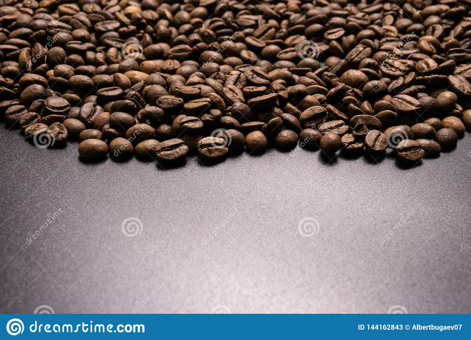 Roasted coffee beans in bulk on a black background. dark cofee roasted grain flavor aroma cafe, natural coffe shop background, top