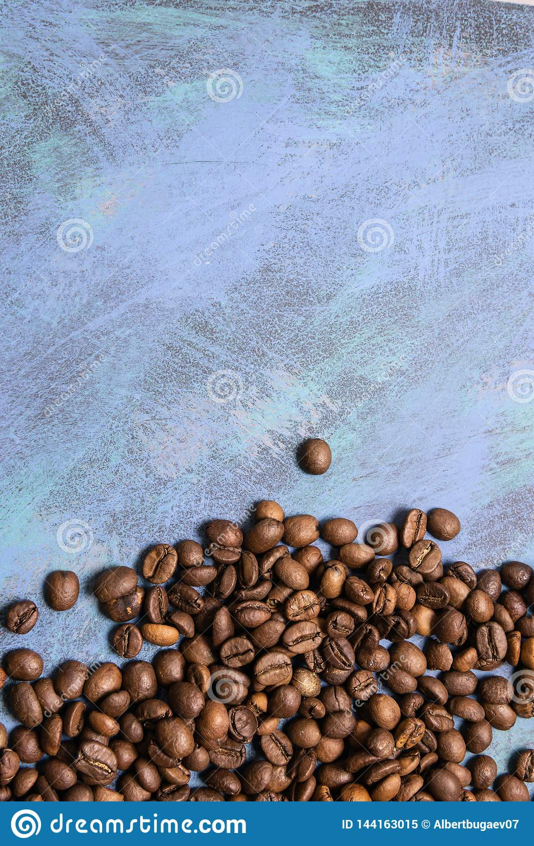 Roasted coffee beans in bulk on a blue background. dark cofee roasted grain flavor aroma cafe, natural coffe shop background, top