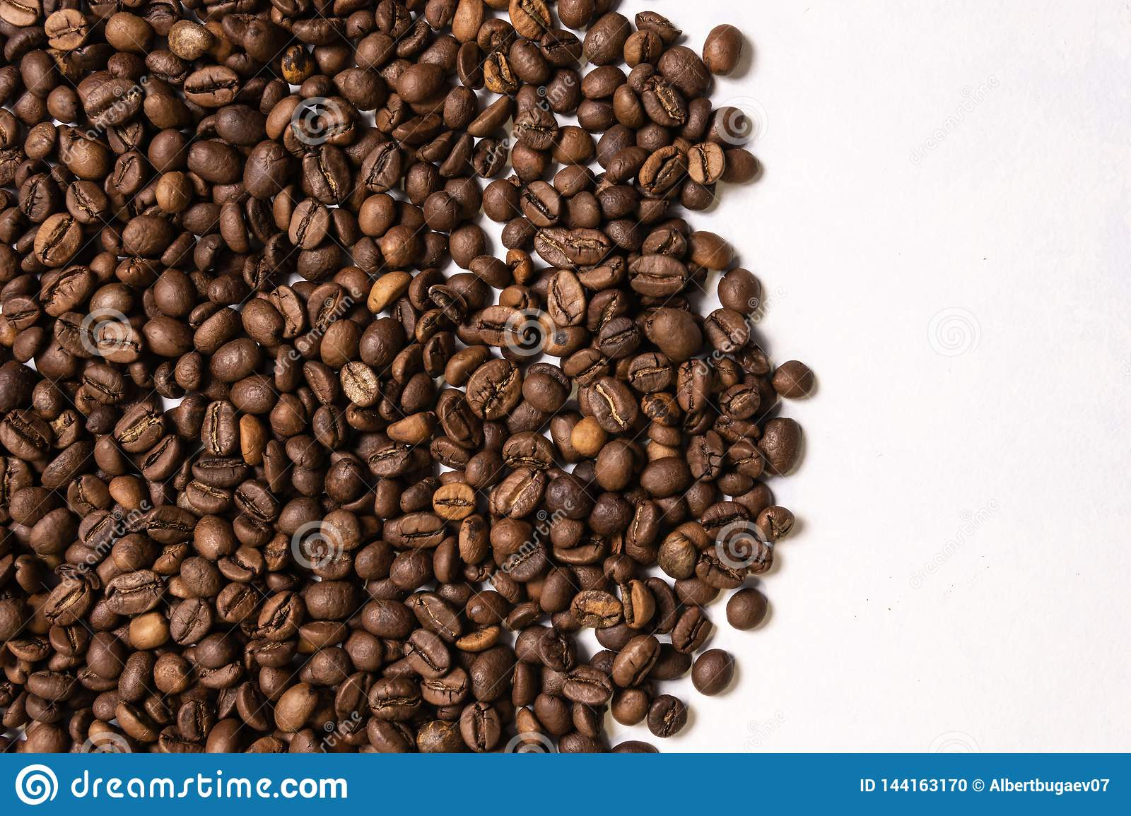 Roasted coffee beans in bulk on a light blue background. dark cofee roasted grain flavor aroma cafe, natural coffe shop background