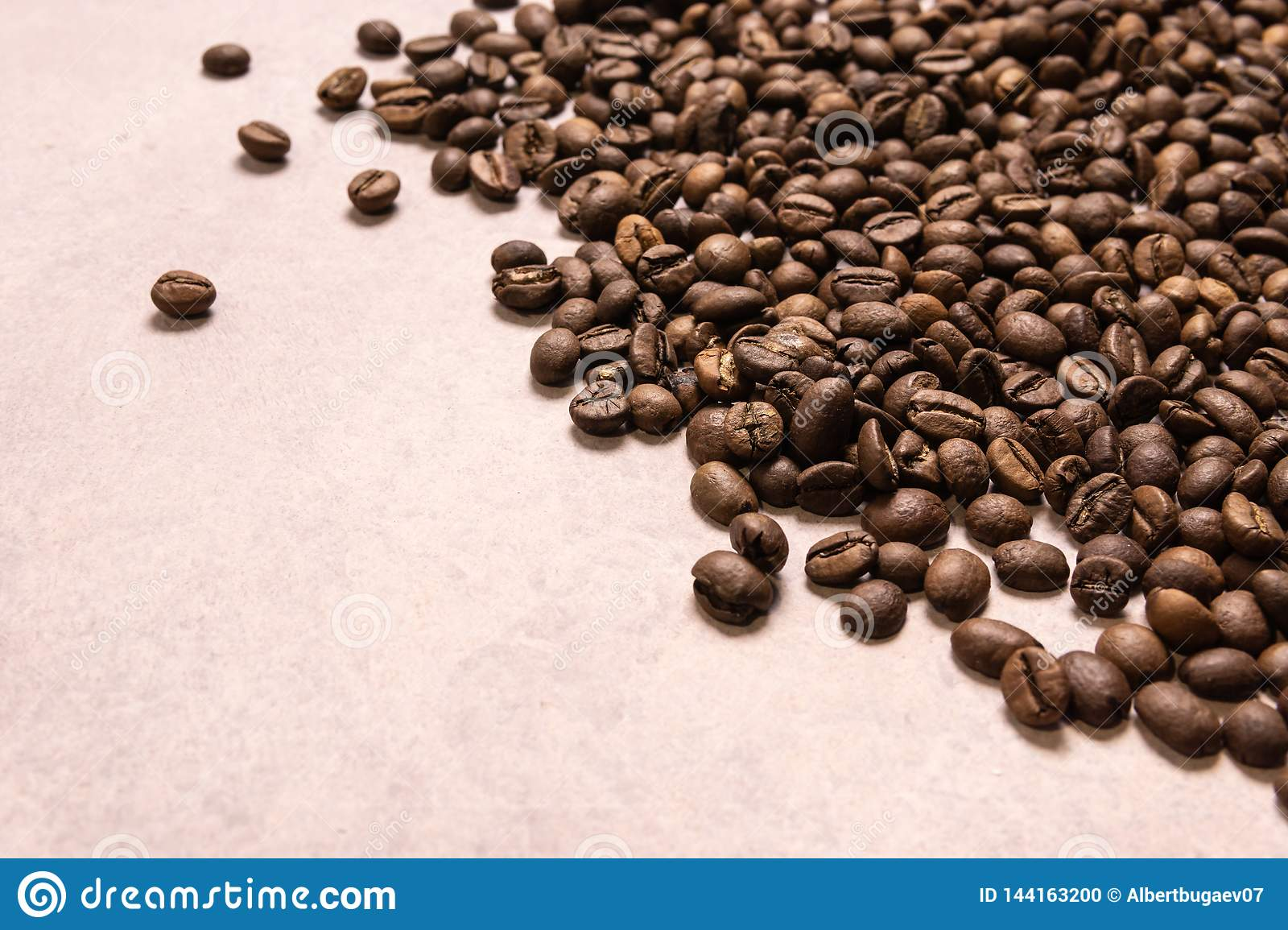 Roasted coffee beans in bulk on a light pink background. dark cofee roasted grain flavor aroma cafe, natural coffe shop background