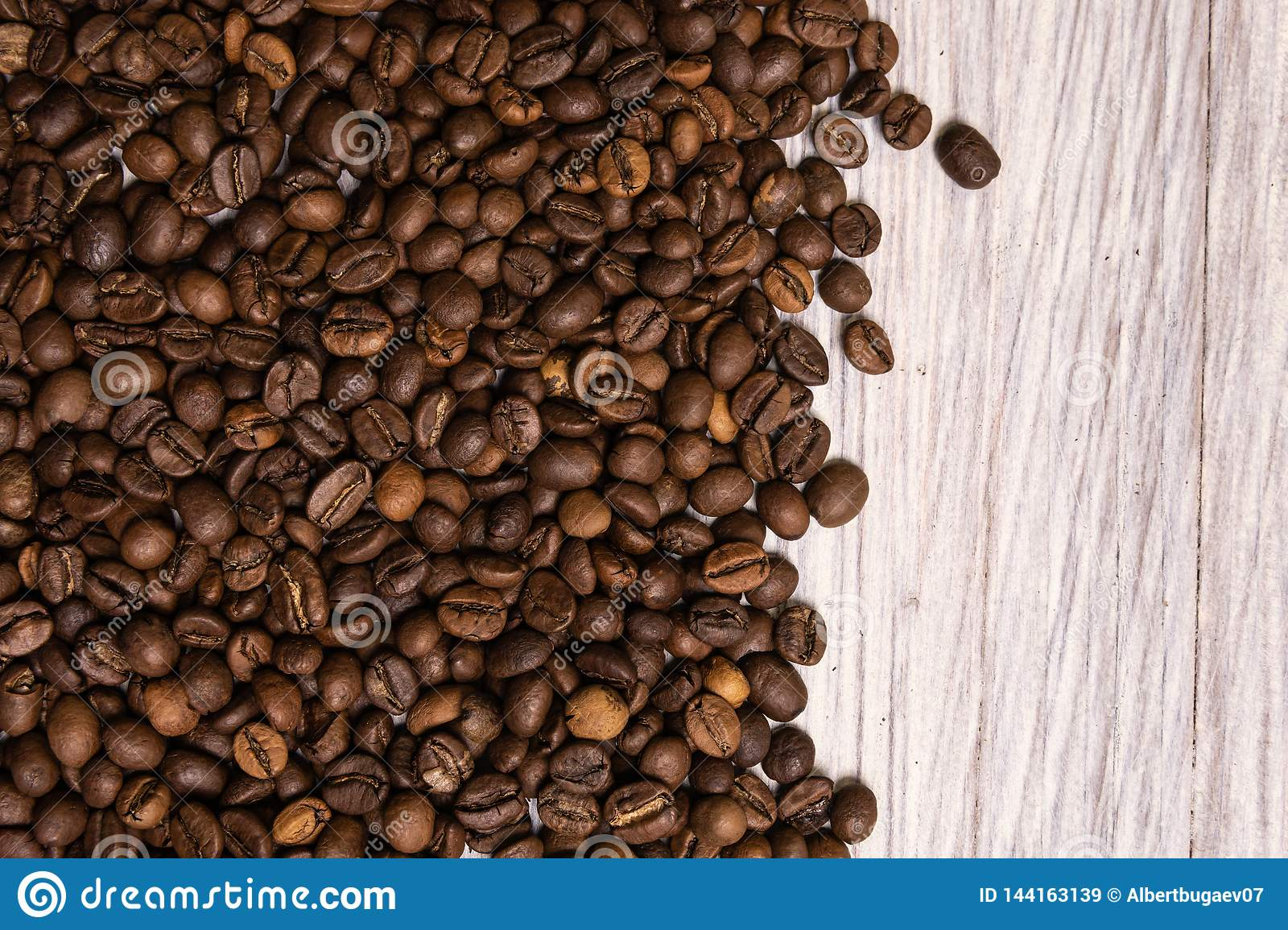 Roasted coffee beans in bulk on a light wooden background. dark cofee roasted grain flavor aroma cafe, natural coffe shop