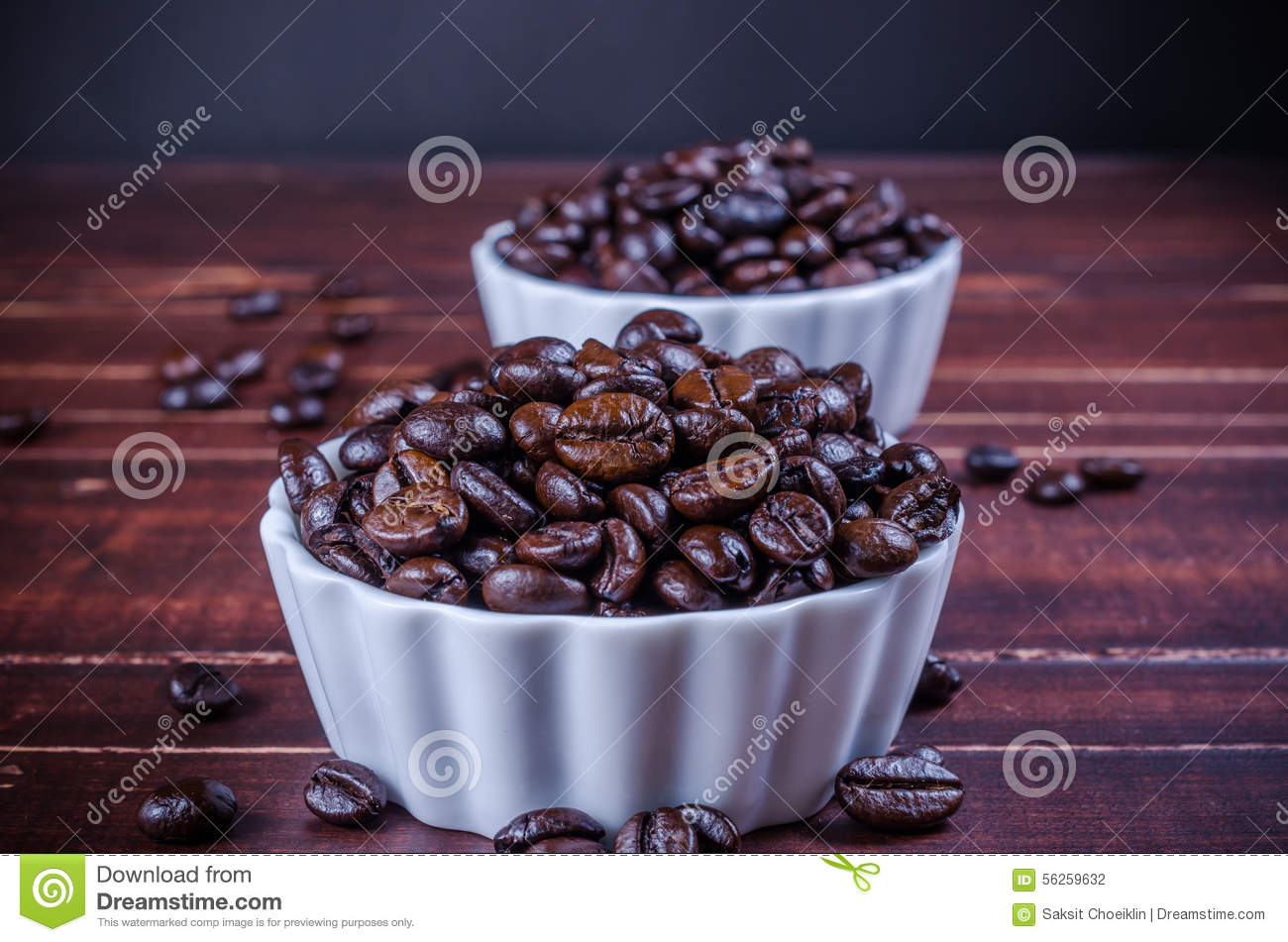 Roasted coffee beans in white bowl porcelain on wooden backg