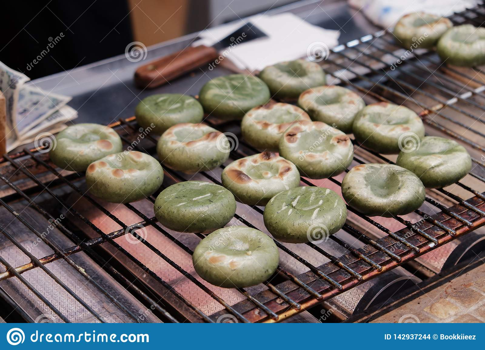 Roasted green tea mochi with red beans inside.