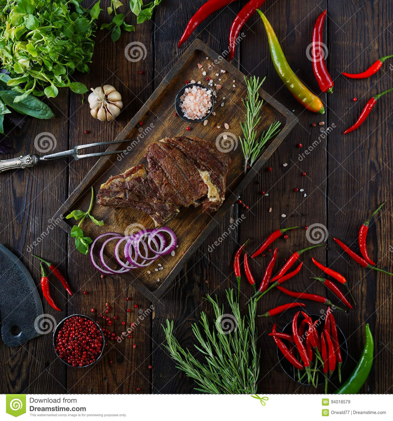 Roasted meat with onions, garlic, spices, fresh herbs, red pepper and salt
