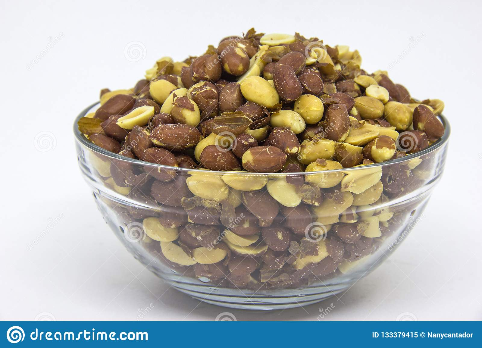 Roasted peanuts in glass bowl on white background