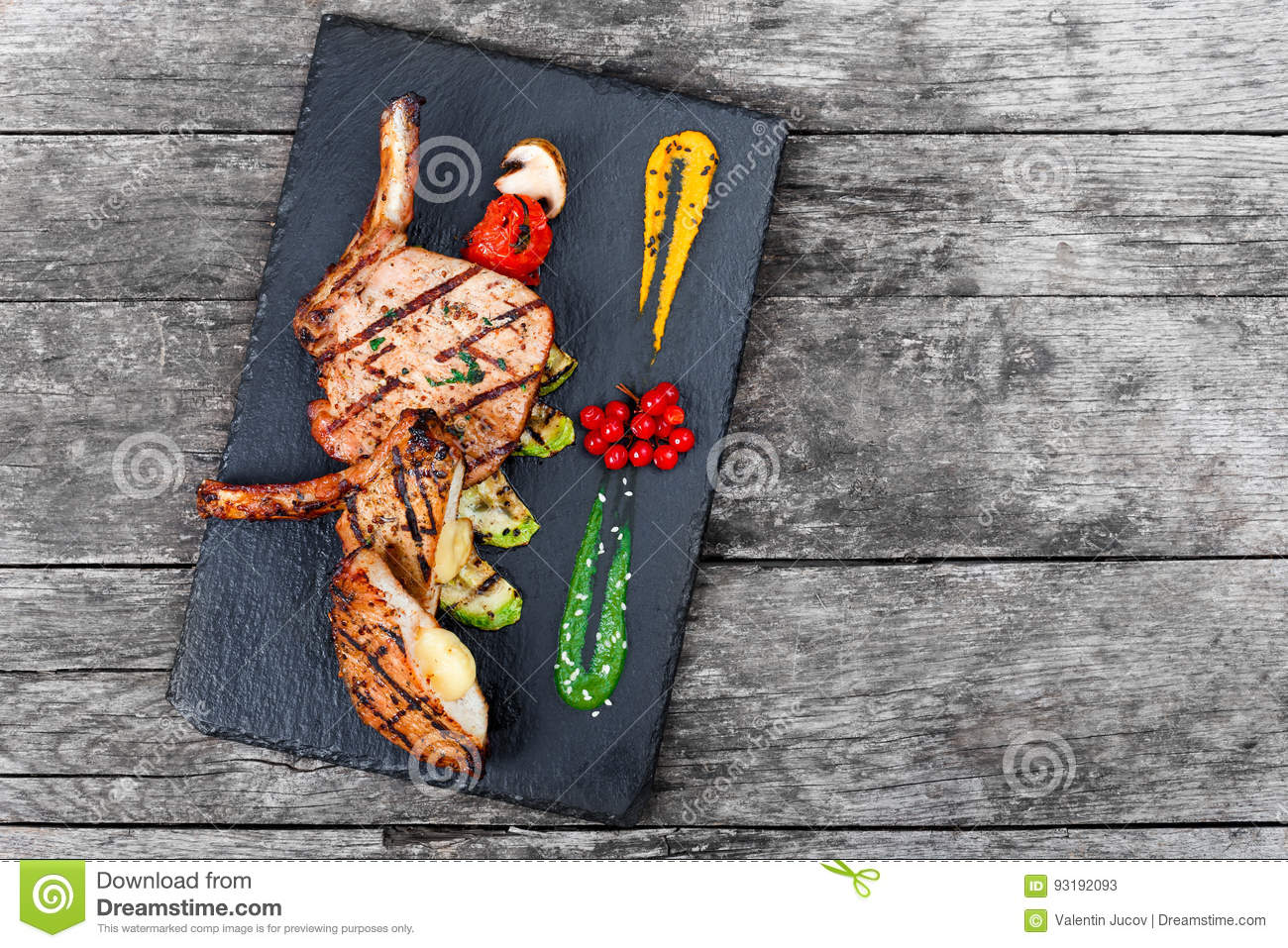 Roasted Pork steak on bone stuffed with cheese, grilled vegetables and berries on stone slate background on wooden background