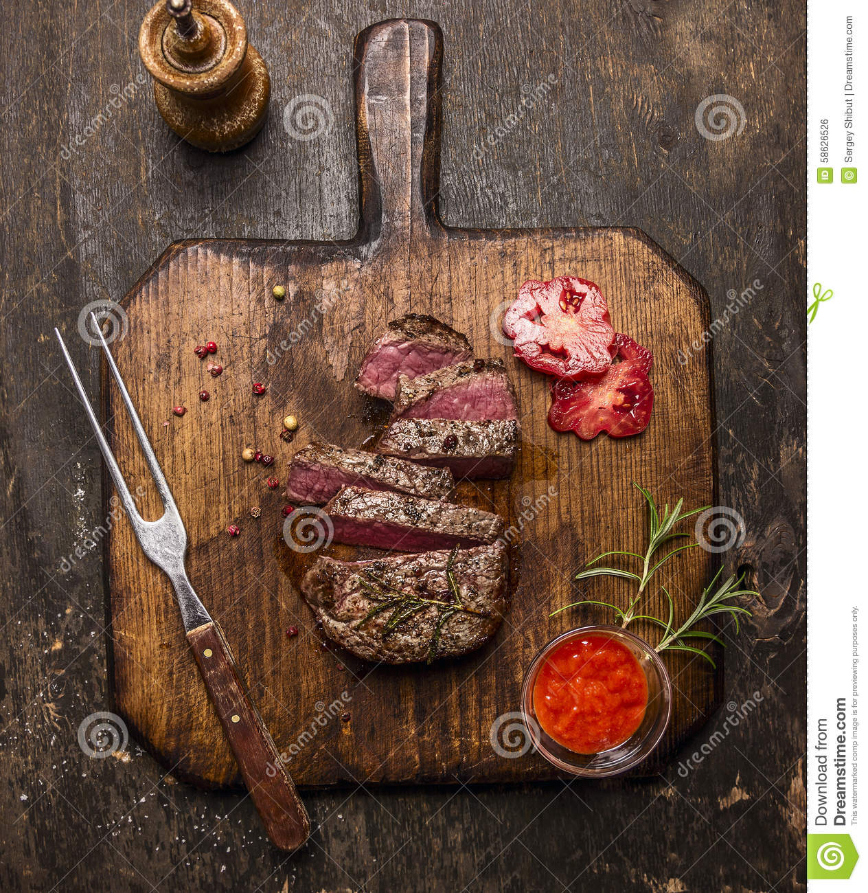 Roasted ribeye steak sliced ​​on a cutting board with a fork, red sauce, peppers and tomatoes on rustic wooden background,