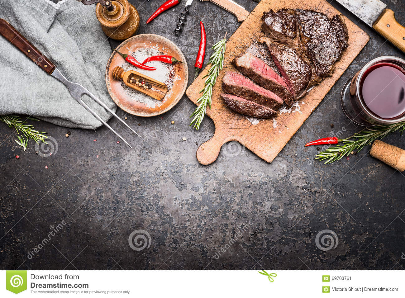 Roasted sliced grill steak on wooden cutting board with wine, seasoning and meat fork on dark vintage metal background, top view