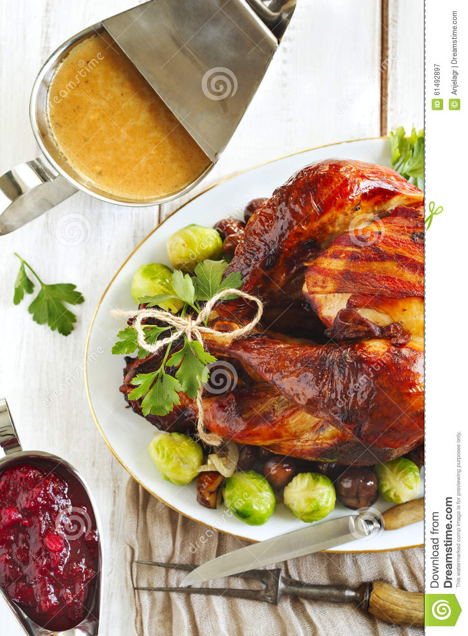 Roasted turkey with bacon and garnished with chestnuts and brussels ...