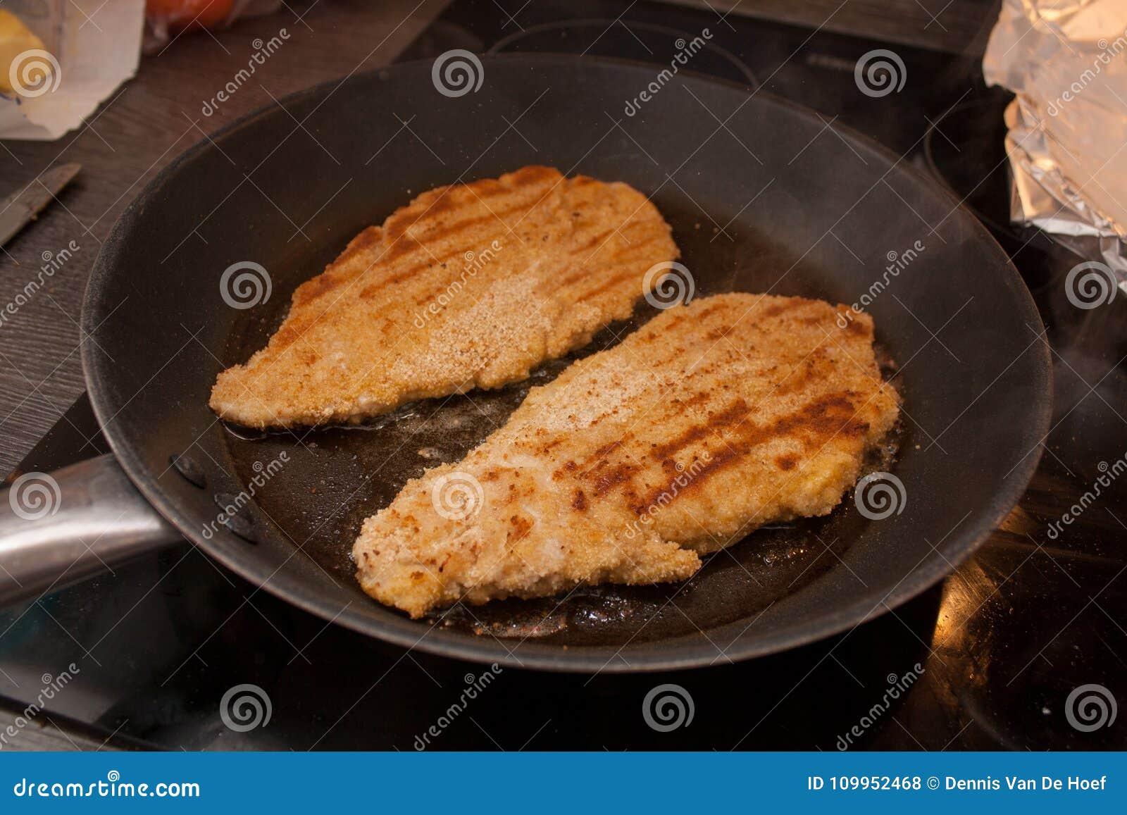 Roasting a wiener schnitzel in a pan.