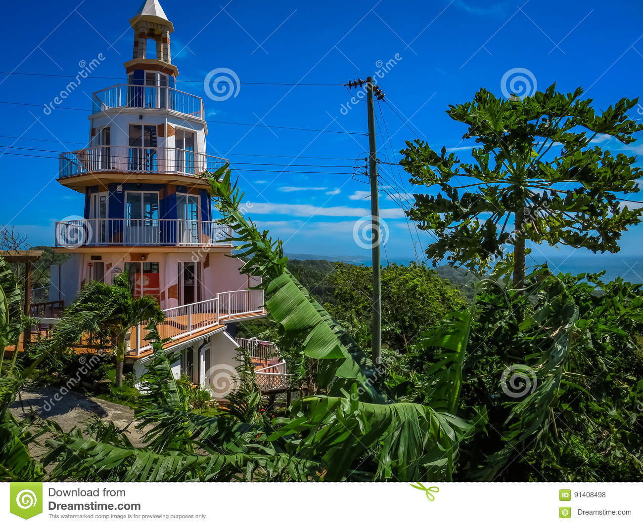 Roatan, Honduras Lighthouse building. Landscape of the island with a blue sky and green vegetation in the background.