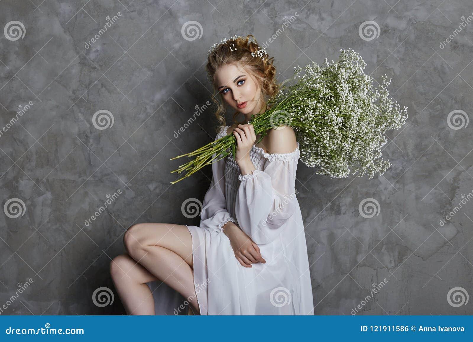 Robe de lumière blanche de fille et cheveux bouclés, portrait de femme avec des fleurs à la maison près de la fenêtre, pureté et