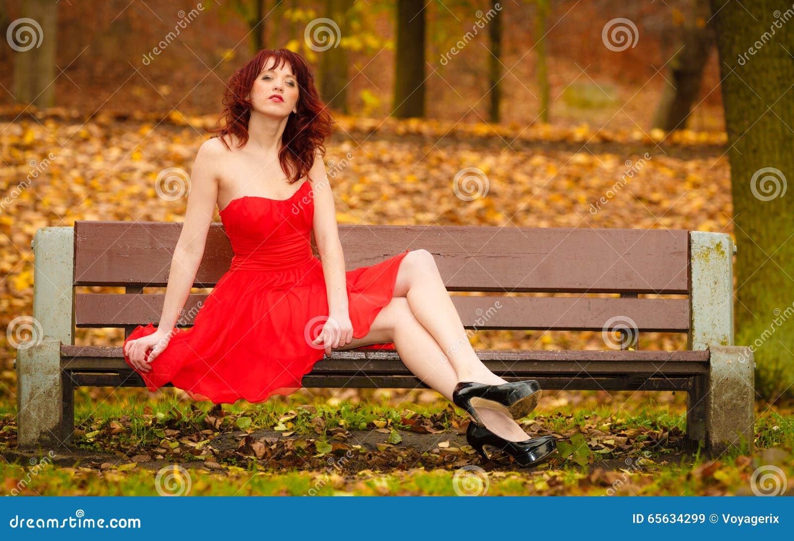 Robe rouge de femme se reposant sur le banc en parc d automne