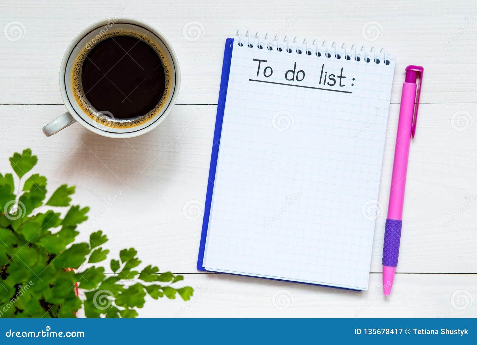 Robić liście pisać w notatniku Notatnik z robić liście na drewnianym biurku z filiżanka kawy