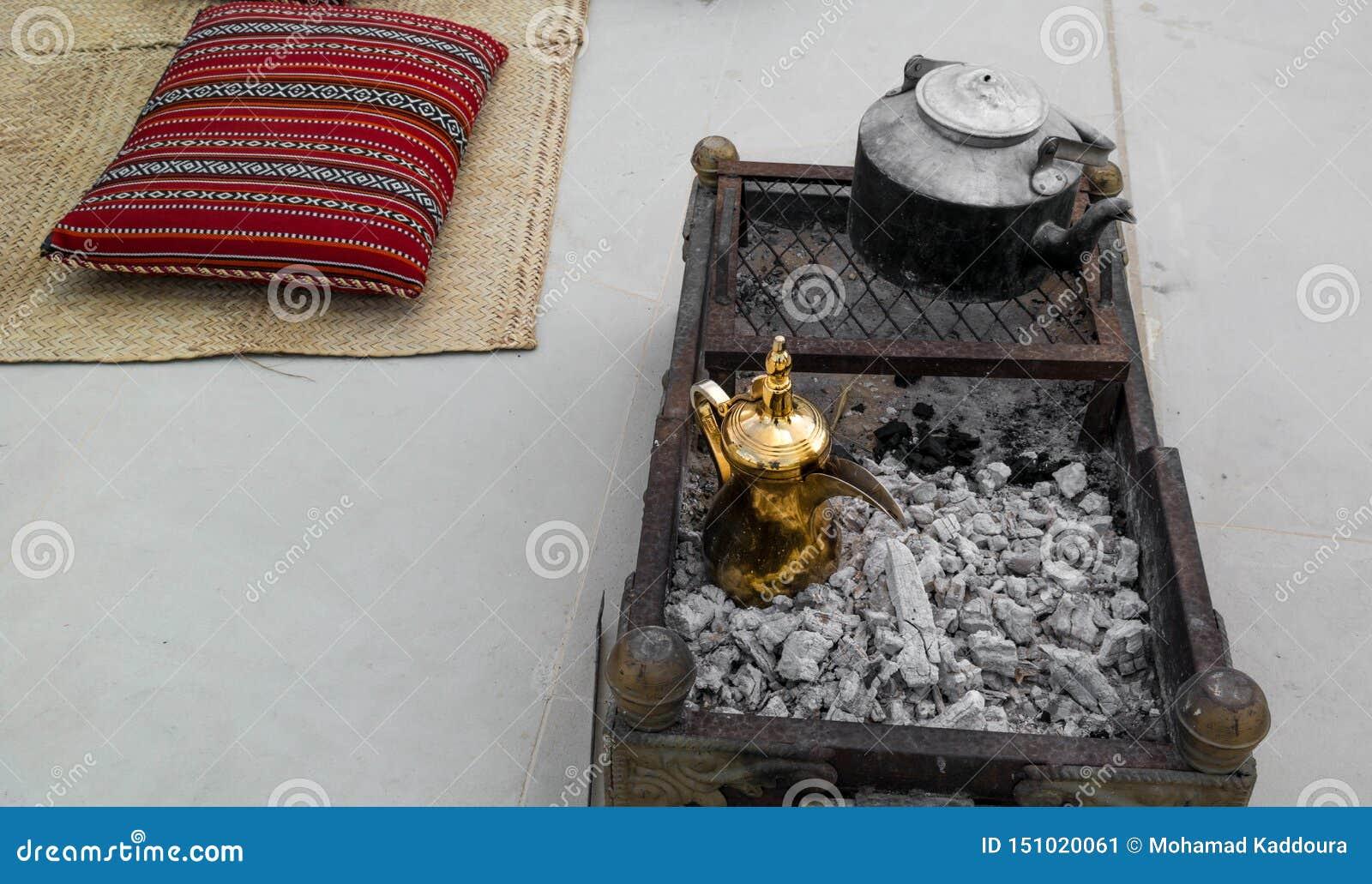Robić tradycyjnej Arabskiej kawie złoty język arabski Dallah na górze węgla drzewnego wokoło Arabskiego decorati i Bliskowschodni