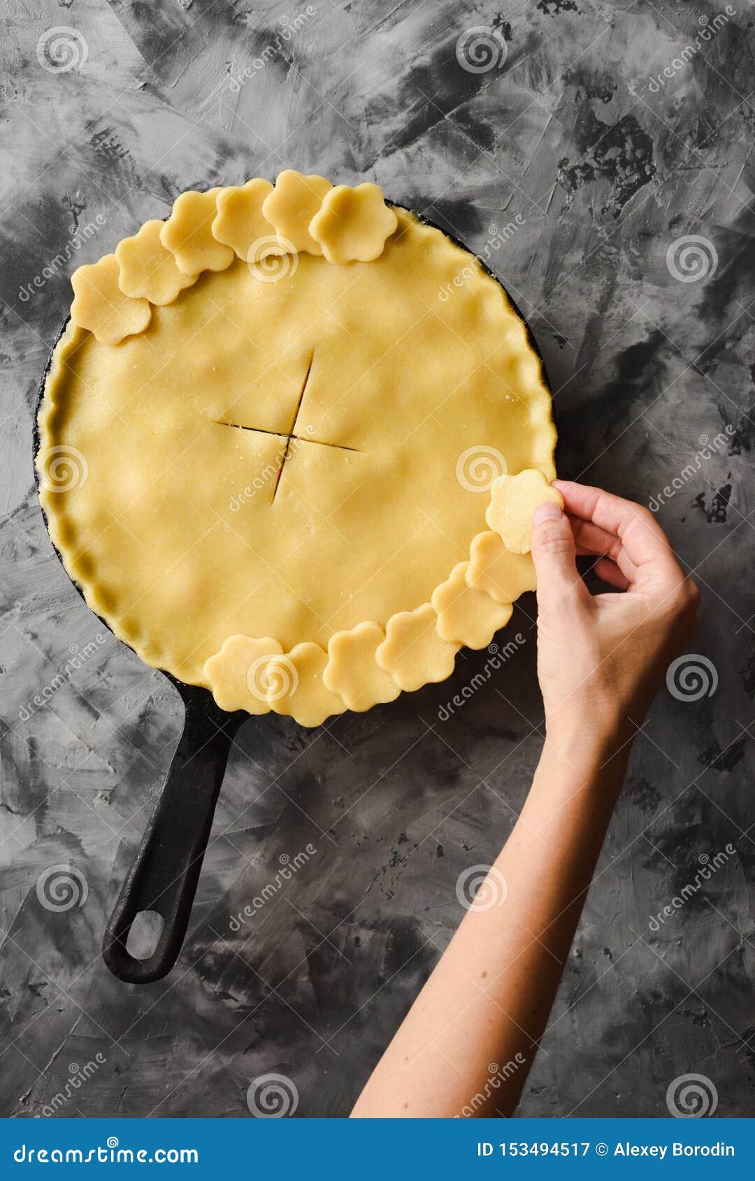 Robić tradycyjnemu jagodowemu kulebiakowi w obsadzie odprasowywa nieckę Nikła kobiety ręka dekoruje skorupę surowy kulebiak przed