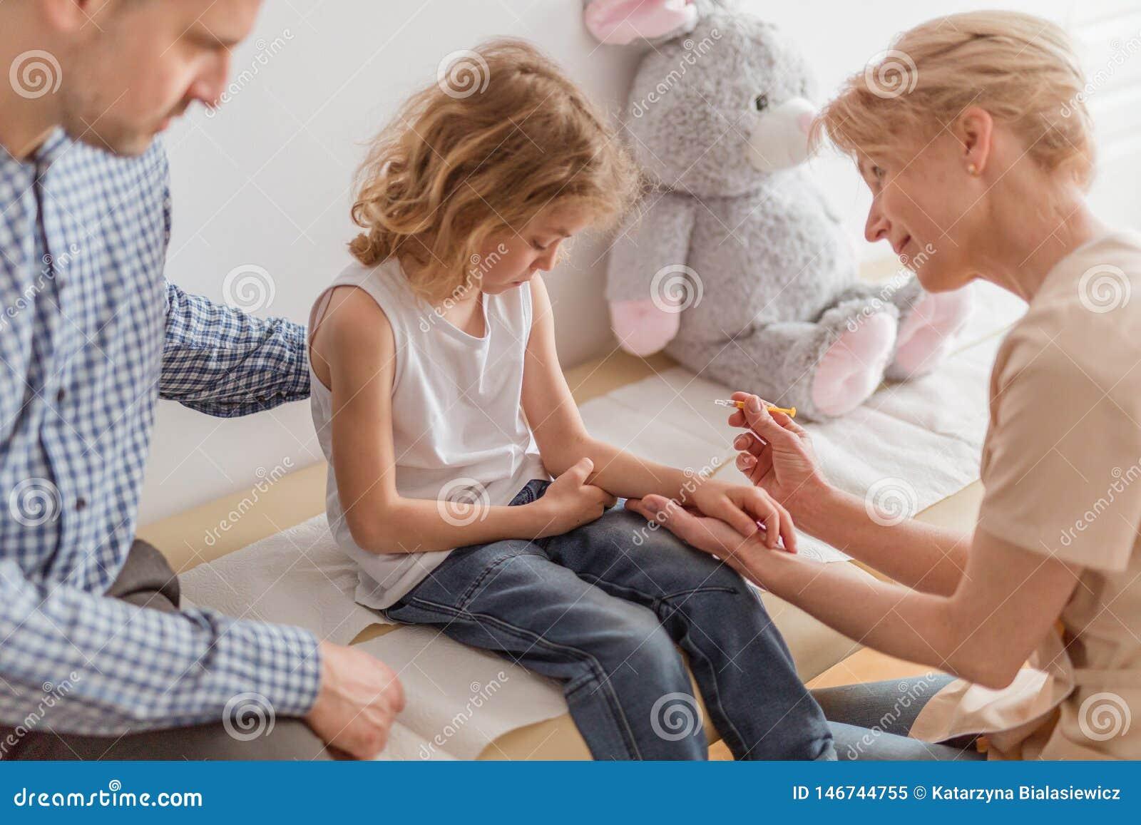 Robić zastrzykowi mała chłopiec podczas wizyty medyczna klinika