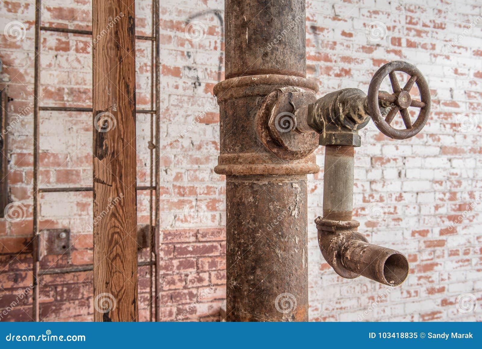 Robinet et tuyau avec l échelle sur le mur de briques rouge