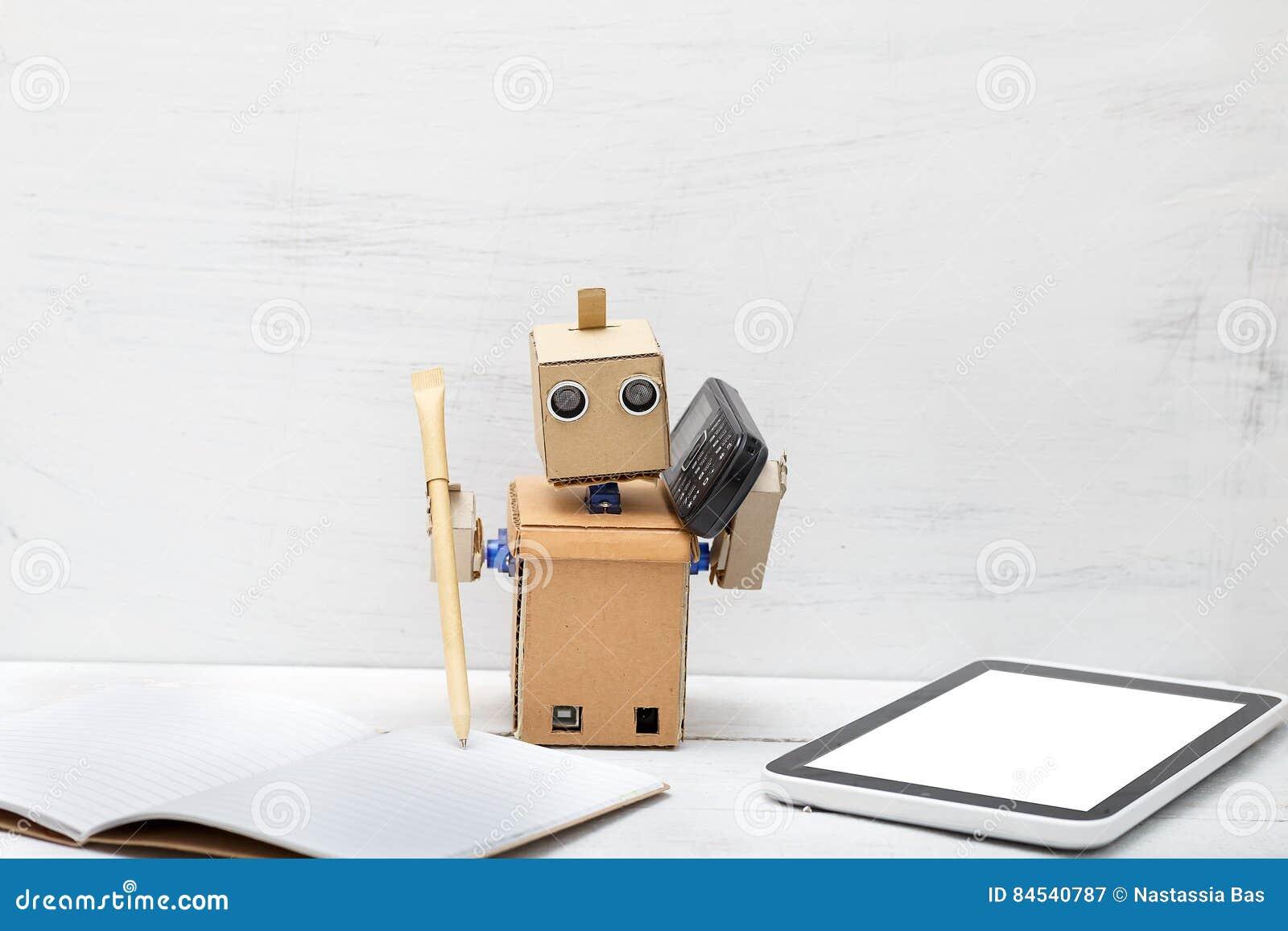 Robot trzyma pióro i telefon jest pobliskim laptopem praca