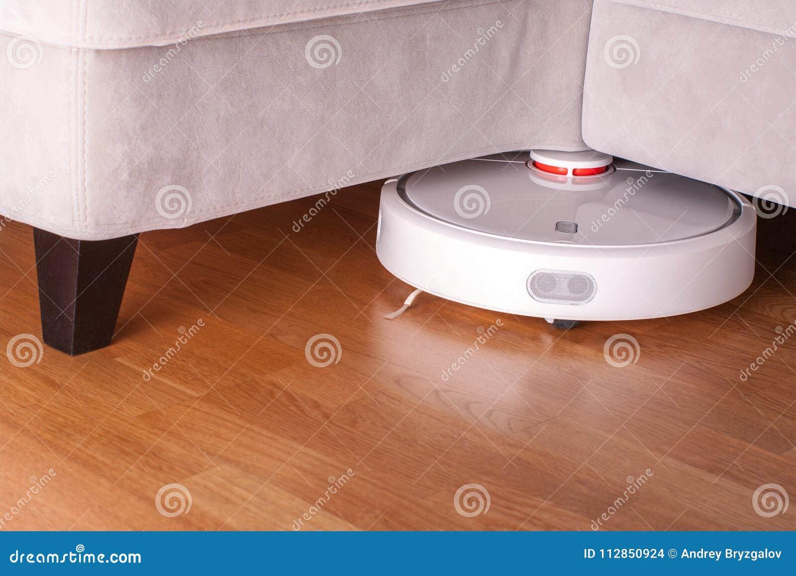 Robotic Vacuum Cleaner Runs Under Sofa In Room On Laminate
