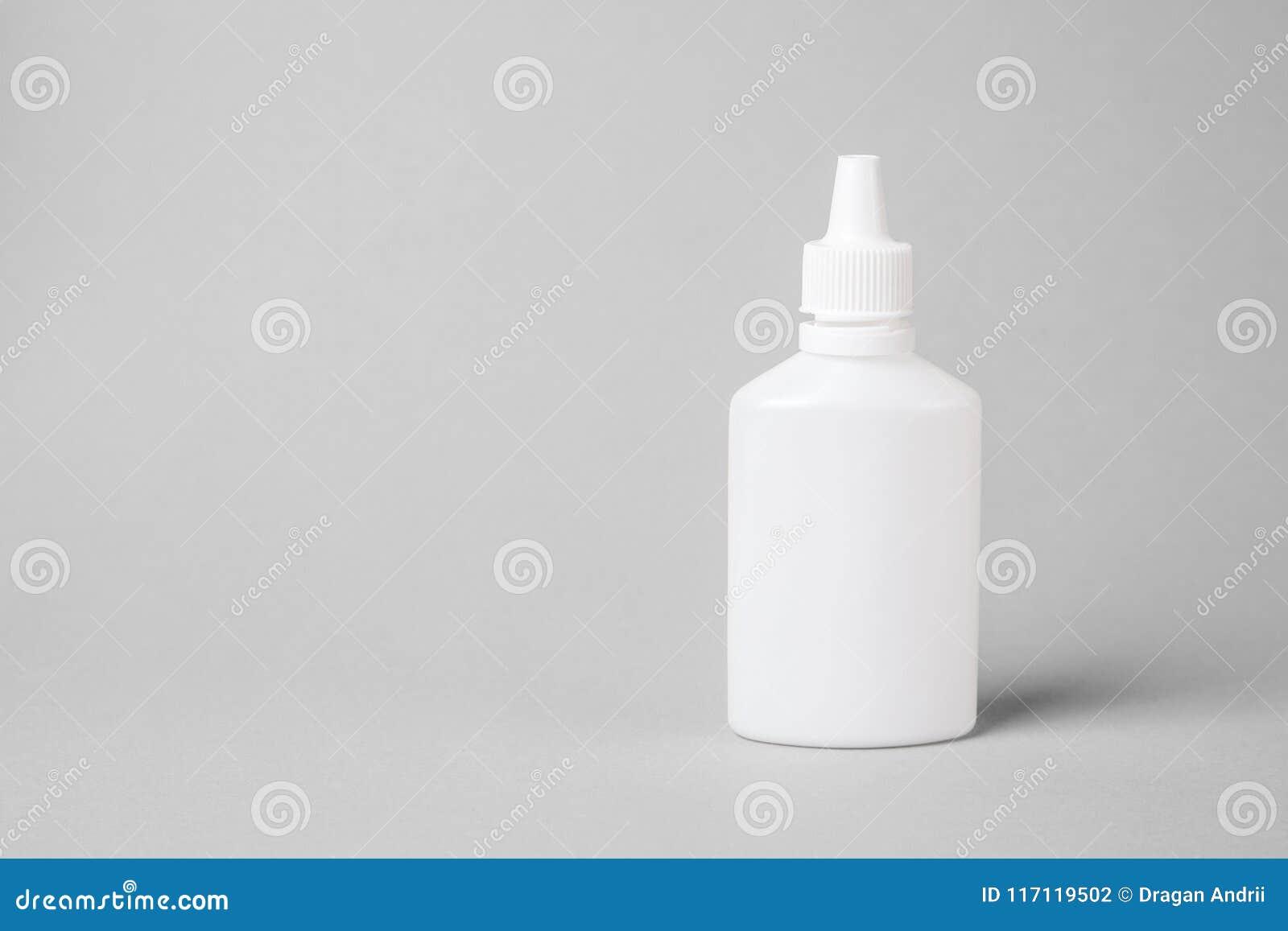 Rocíe para la nariz en una botella plástica blanca en un fondo gris Aerosol del frío común o de la alergia