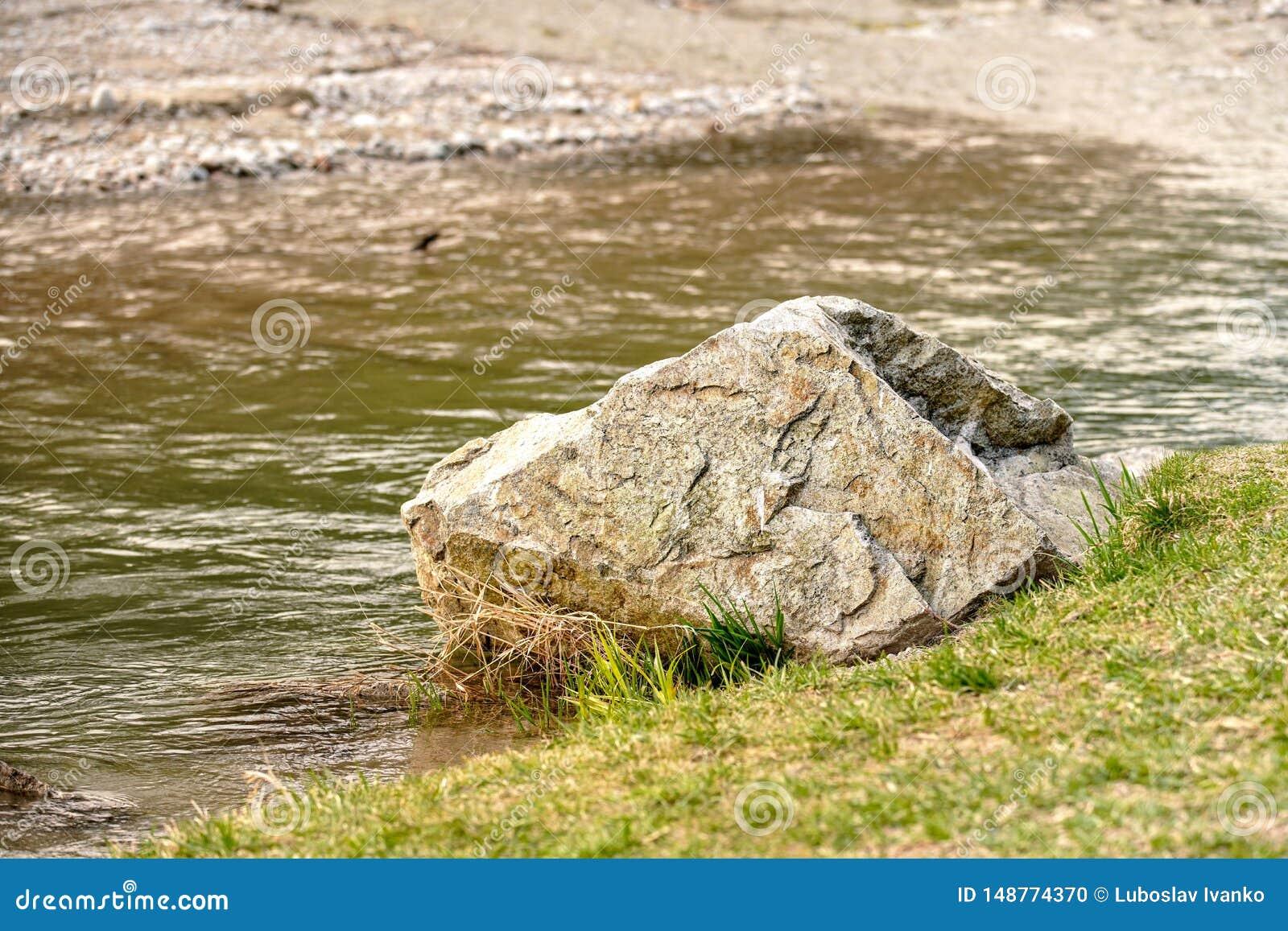 Roca grande del canto rodado en el lado de la hierba del r?o