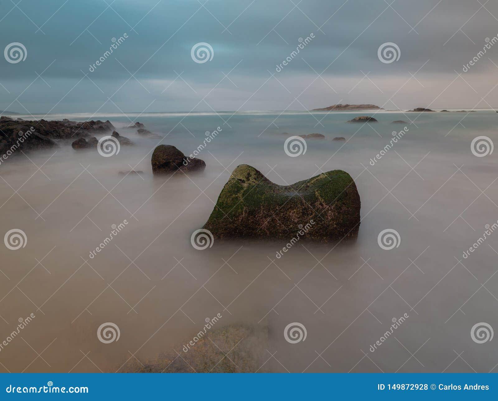Roca grande en una playa española con una isla en el fondo