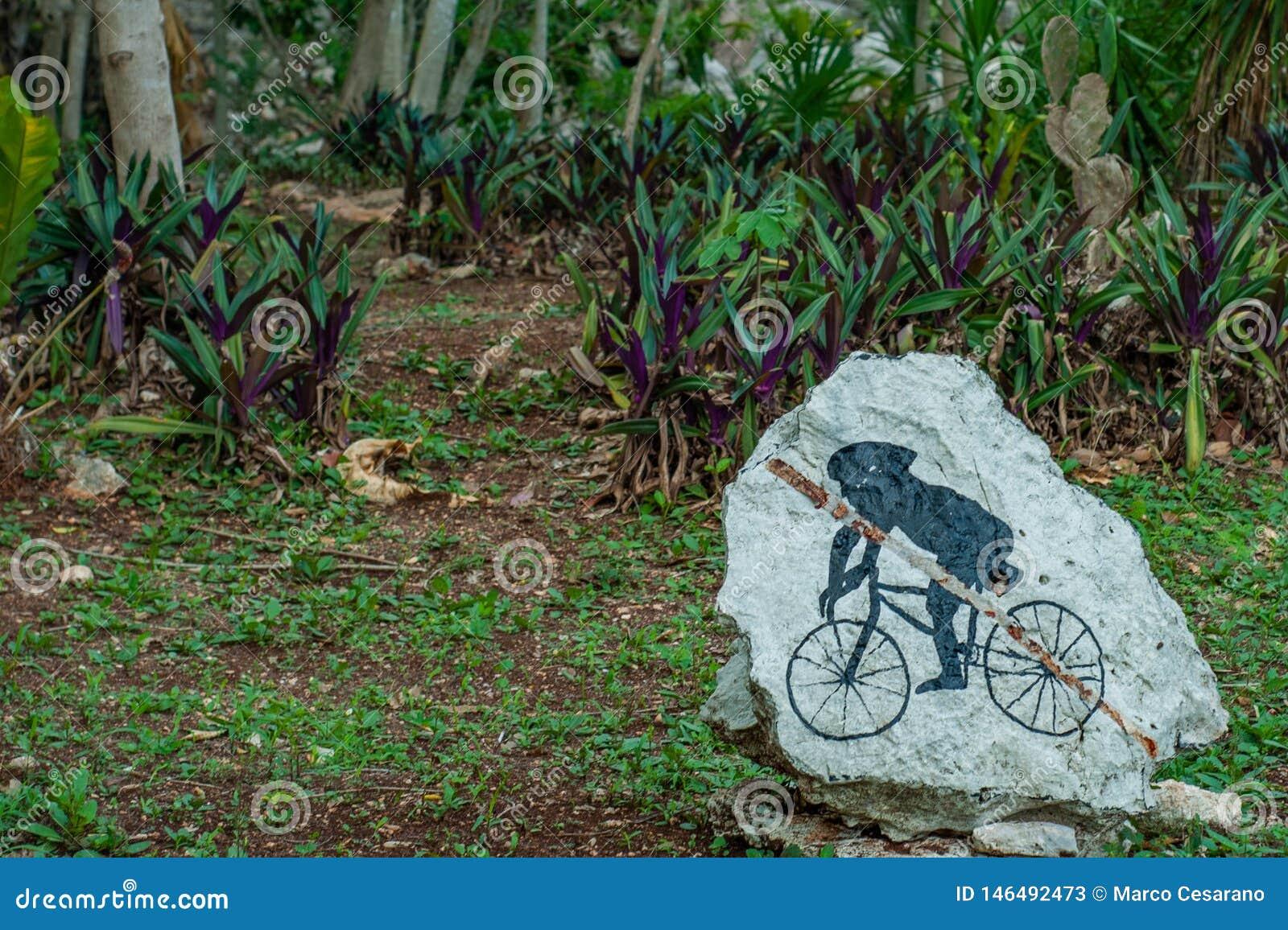 Roca restaurada, representando una Maya joven en una bicicleta, admitida las ruinas del área arqueológica de Ek Balam
