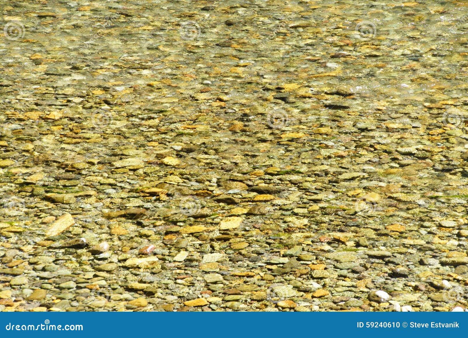 Rocas lisas del río en la corriente
